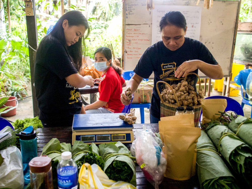 Anjelen and her team weigh and pack produce that will be sold at their community market. Photo: Natasha Sim